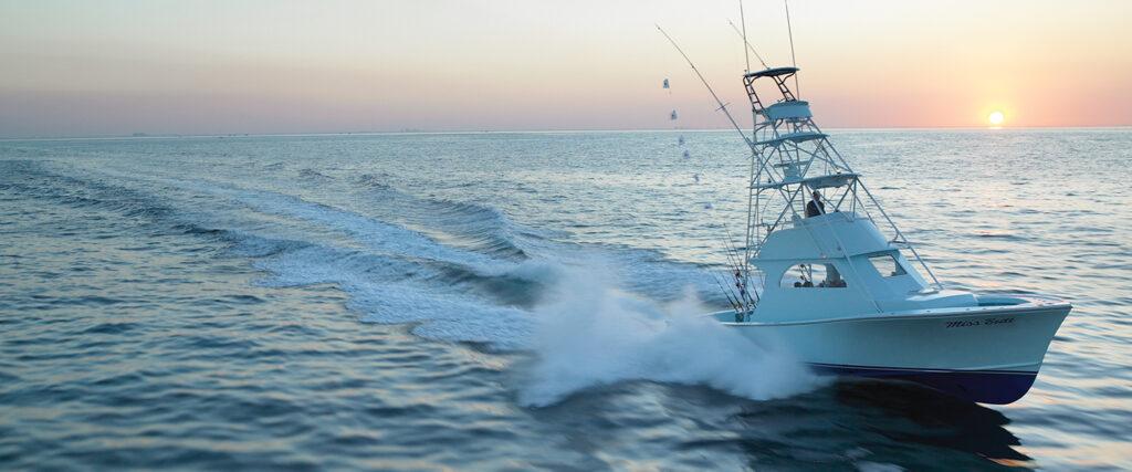 Båt i hög fart med solnedgång i bakgrunden